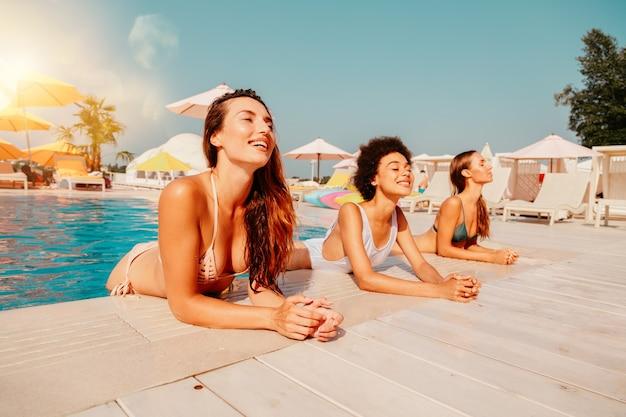 Grupo de amigos de maiô curtindo em uma piscina
