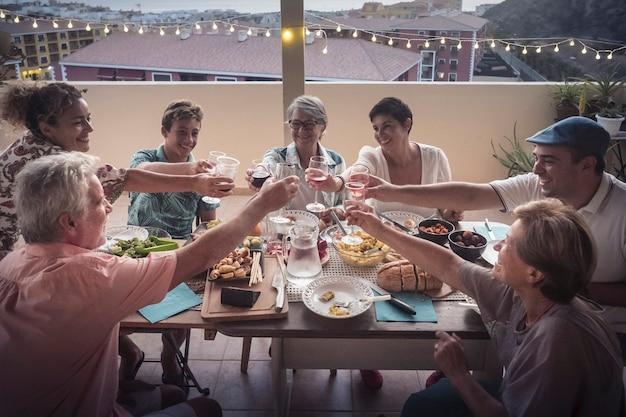 Grupo de amigos de várias idades brindando com copos jantando à noite em casa