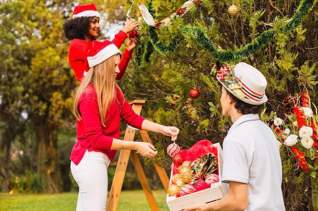 Grupo de amigos decorando uma árvore de natal