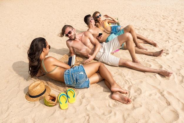 Grupo de amigos deitado na praia tomando banho de sol