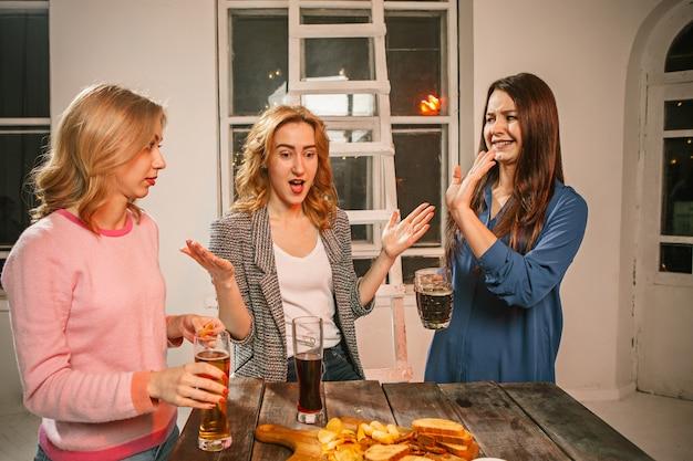 Grupo de amigos, desfrutando de bebidas à noite com cerveja na mesa de madeira