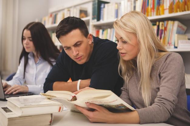 Grupo de amigos, desfrutando de estudar juntos na biblioteca
