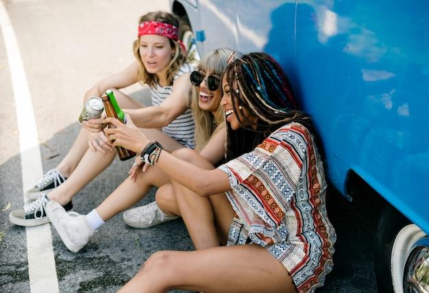 Grupo de amigos diversos bebendo cerveja álcool juntos pelo van Foto Premium
