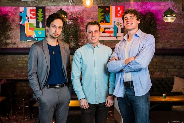 Grupo de amigos do sexo masculino em bar a sorrir