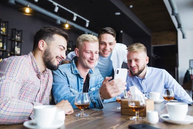 Grupo de amigos do sexo masculino olhando para smartphone sentado no restaurante com bebidas na mesa