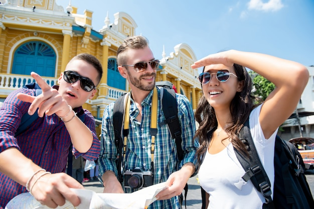 Grupo de amigos do turista que procuram a direção ao viajar em banguecoque tailândia