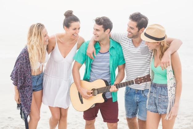 Grupo de amigos em pé na praia com um violão