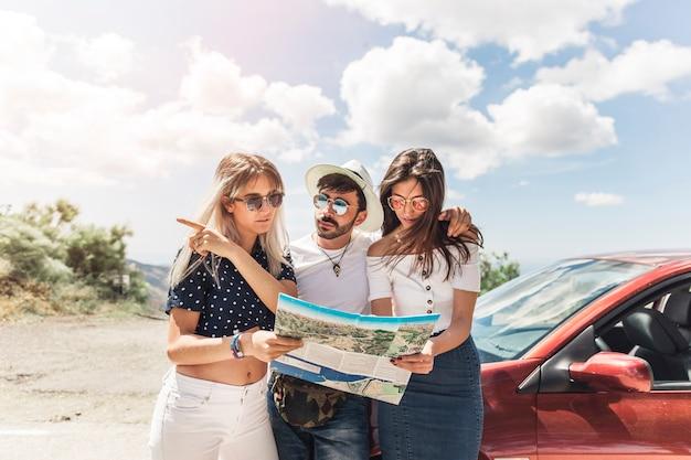 Grupo de amigos em pé perto do carro olhando mapa