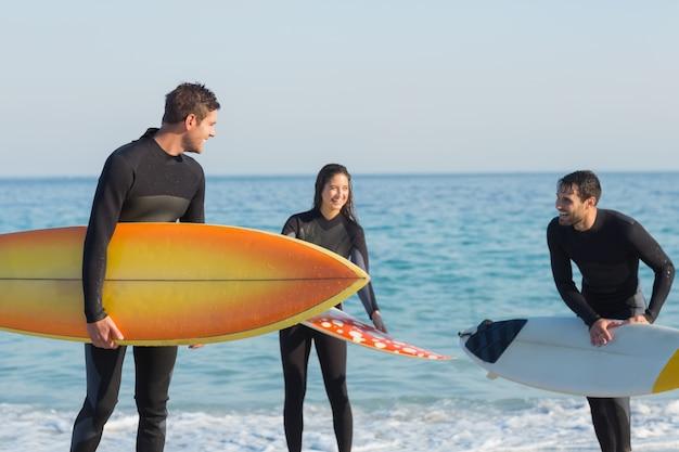 Grupo de amigos em roupa de mergulho com prancha de surf em um dia ensolarado