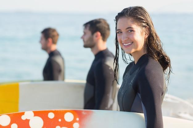 Grupo de amigos em roupas de mergulho com uma prancha de surf em um dia ensolarado