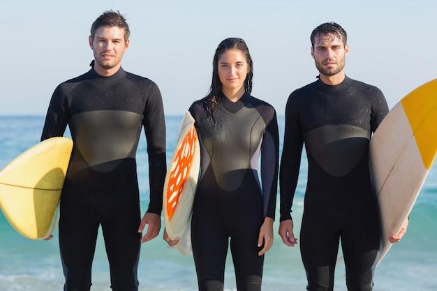 Grupo de amigos em roupas de neoprene com uma prancha de surfe em um dia ensolarado