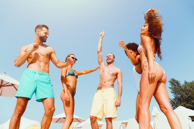 Grupo de amigos em traje de banho dance music em uma piscina
