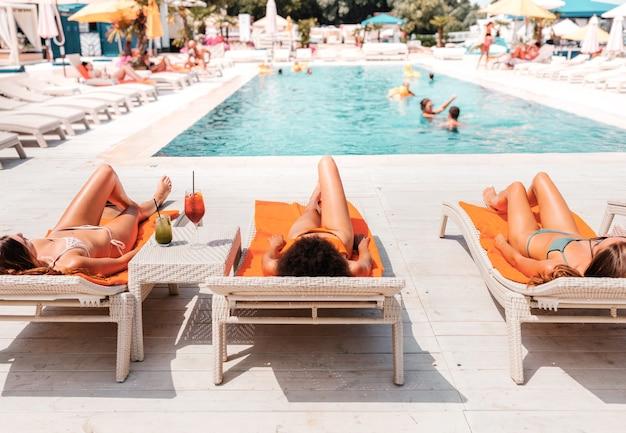 Grupo de amigos em traje de banho toma um coquetel em uma piscina