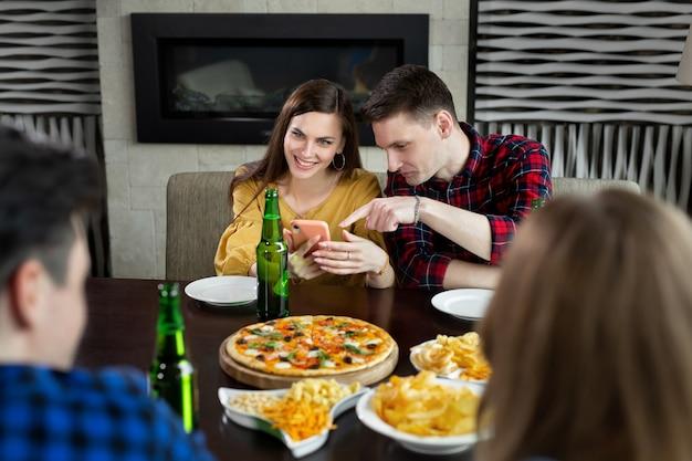 Grupo de amigos em um café com pizza e cerveja se divertindo