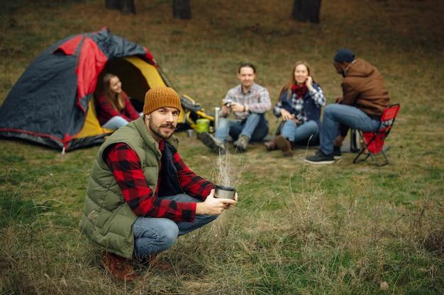 Grupo de amigos em uma viagem de acampamento ou caminhada em dia de outono. homens e mulheres com bolsa turística fazendo intervalo na floresta, conversando, rindo. atividade de lazer, amizade, fim de semana. beba na garrafa térmica.