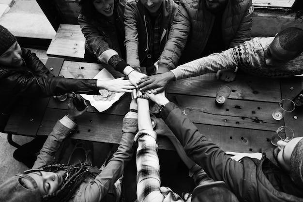 Grupo de amigos empilhando as mãos