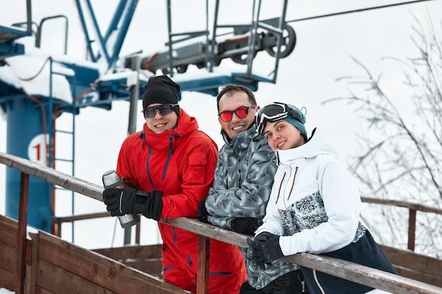Grupo de amigos esquiadores na montanha está descansando e bebendo café em uma garrafa térmica no fundo do teleférico.