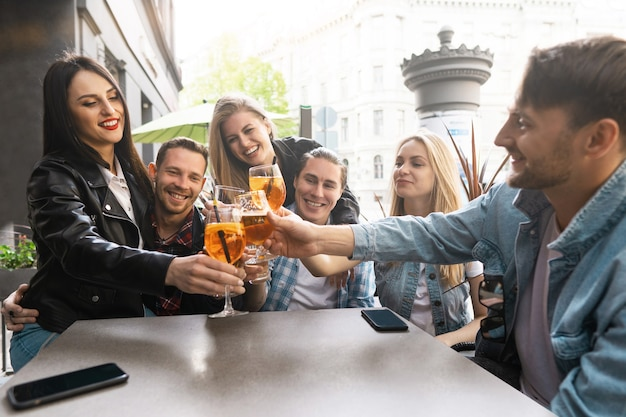 Grupo de amigos está feliz em se ver. comemorando encontro no bar da rua.