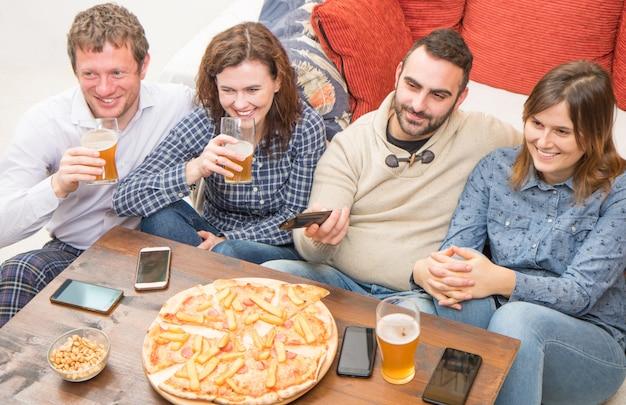 Grupo de amigos estão bebendo cerveja, comendo pizza, conversando e sorrindo enquanto descansa em casa