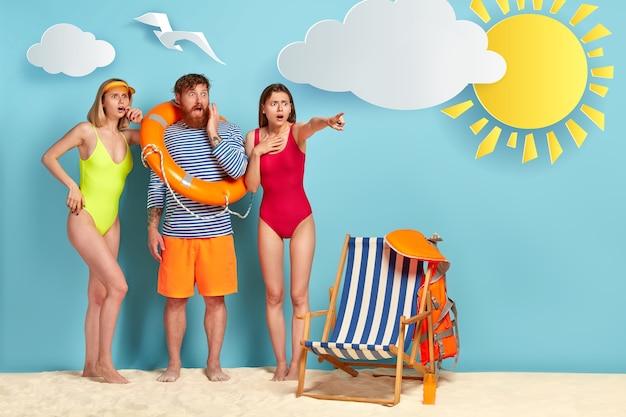 Grupo de amigos estupefatos posando na praia