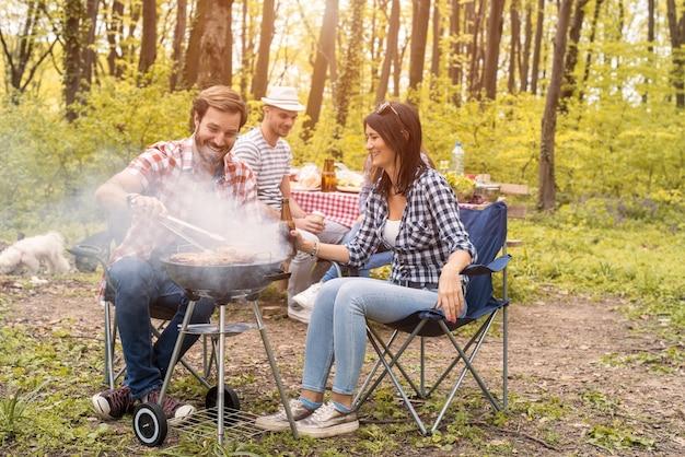 Grupo de amigos fazendo churrasco na floresta no verão