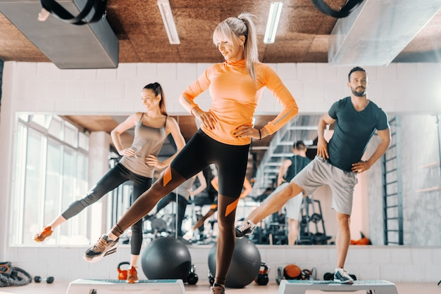 Grupo de amigos fazendo exercícios de fitness para as pernas no ginásio. no fundo, seu reflexo no espelho.
