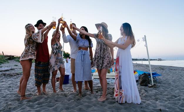 Grupo de amigos fazendo festa na praia na hora por do sol