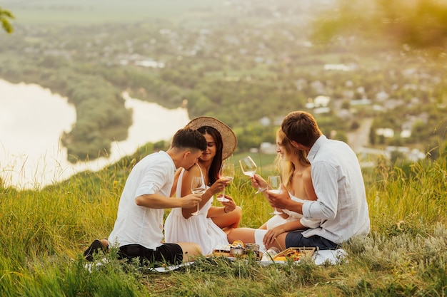 Grupo de amigos fazendo piquenique na natureza.