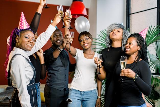 Grupo de amigos felizes africanos bebendo champanhe e comemorando o ano novo. festa de ano novo. festa de aniversário