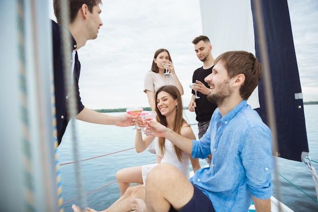 Grupo de amigos felizes bebendo cocktails de vodka em um barco