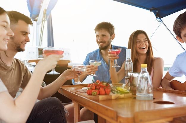 Grupo de amigos felizes bebendo coquetéis de vodka em uma festa de barco ao ar livre