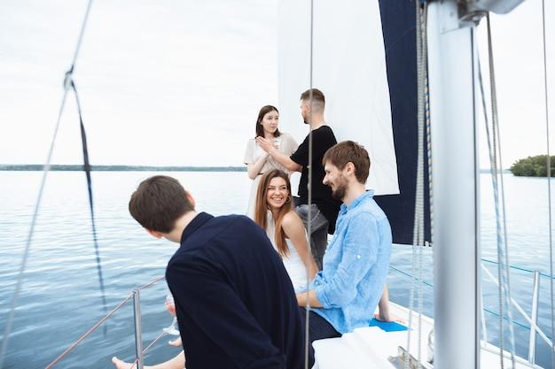 Grupo de amigos felizes bebendo coquetéis de vodka em uma festa no barco ao ar livre, no verão