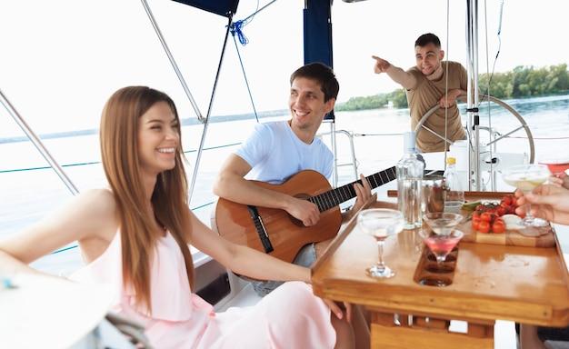 Grupo de amigos felizes bebendo coquetéis de vodka na festa do barco ao ar livre, alegre e feliz. jovens se divertindo no conceito de passeio, juventude e férias de verão do mar. álcool, férias, descanso.