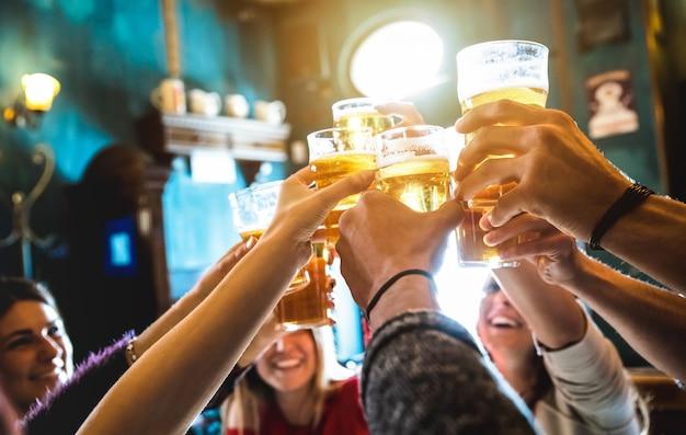 Grupo de amigos felizes bebendo e brindando cerveja em bar