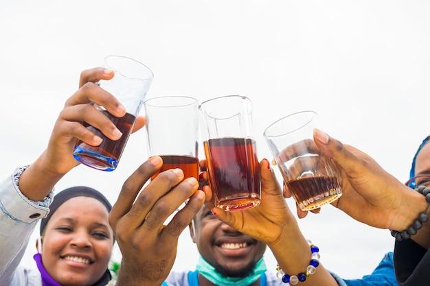 Grupo de amigos felizes bebendo e brindando com urso - conceito de amizade com jovens fazendo festa juntos - foco na taça de vinho