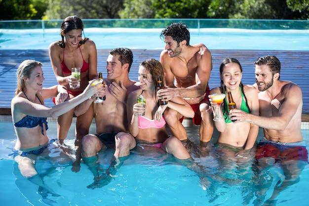Grupo de amigos felizes brindando com garrafas de cerveja e um copo de coquetel