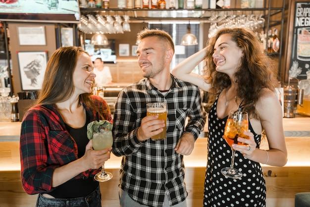 Grupo de amigos felizes com bebidas no bar