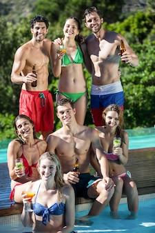 Grupo de amigos felizes com garrafas de cerveja e um copo de coquetel