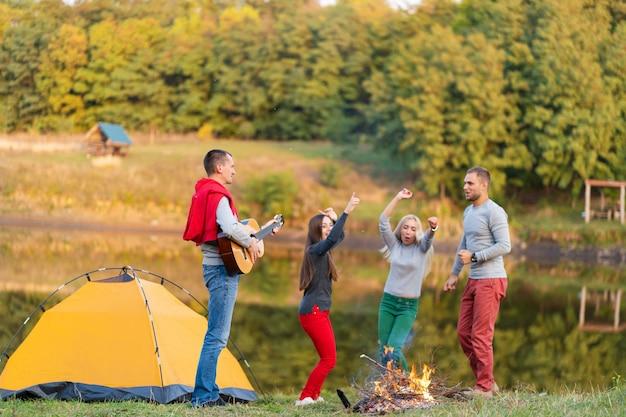 Grupo de amigos felizes com guitarra, se divertindo ao ar livre, dançando e pulando perto do lago no fundo do parque, o lindo céu. diversão em camping