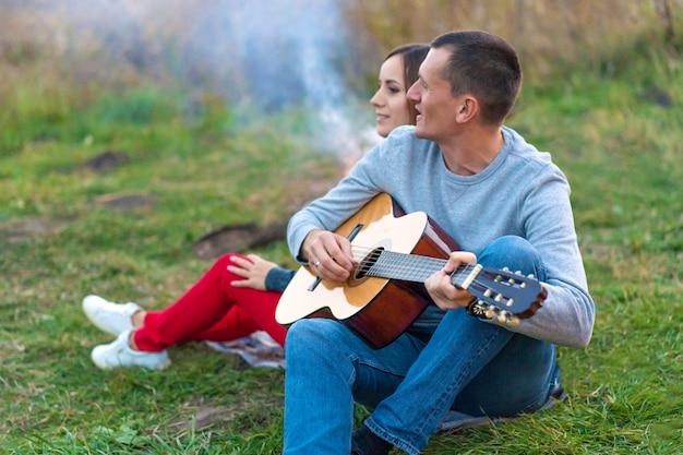 Grupo de amigos felizes com guitarra, se divertindo ao ar livre, perto da barraca da fogueira e do turista. diversão de acampamento família feliz
