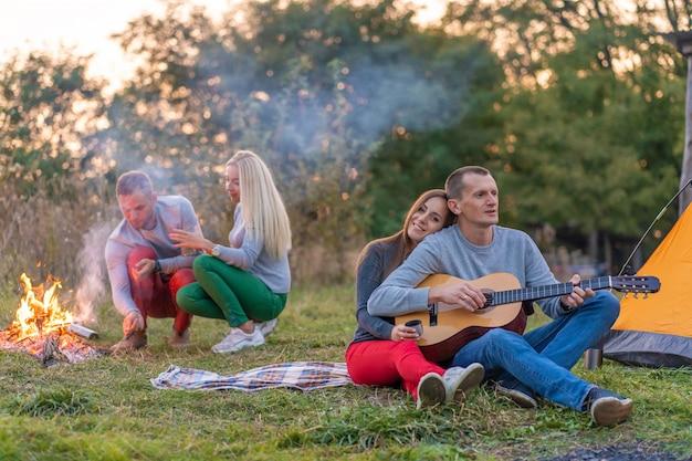 Grupo de amigos felizes com guitarra, se divertindo ao ar livre, perto da barraca da fogueira e do turista