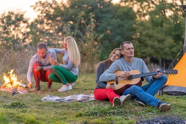 Grupo de amigos felizes com guitarra, se divertindo ao ar livre, perto da barraca da fogueira e do turista.