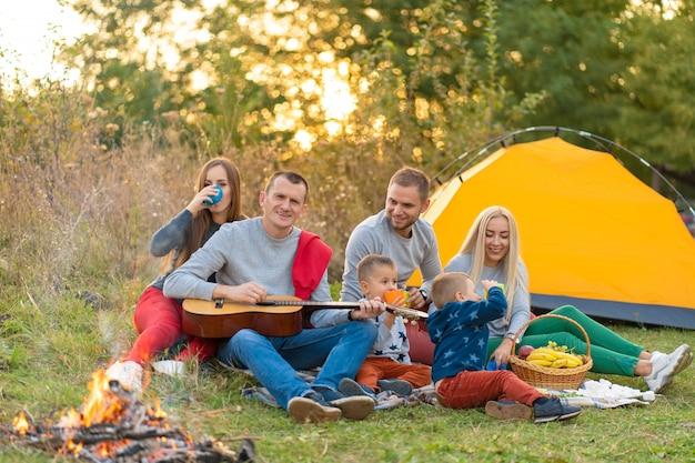 Grupo de amigos felizes com tenda e bebidas tocando violão no camping