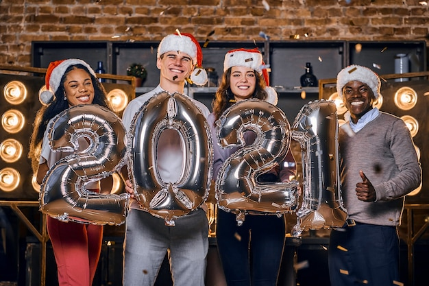 Grupo de amigos felizes comemorando o ano novo junto com balões.