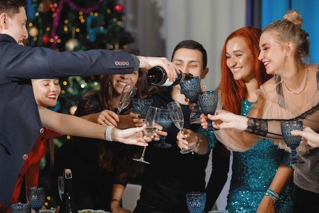 Grupo de amigos felizes comemorando o natal ou ano novo. um homem derrama champanhe em taças. mulheres riem, sentadas à mesa perto da árvore de natal.