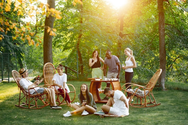 Grupo de amigos felizes comendo e bebendo cerveja em um jantar de churrasco na hora do pôr do sol