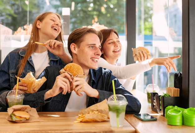 Grupo de amigos felizes comendo hambúrgueres