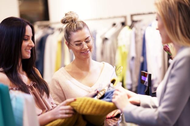 Grupo de amigos felizes comprando roupas no shopping