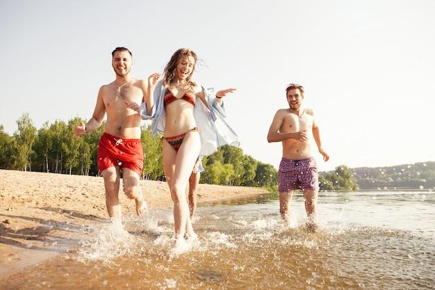 Grupo de amigos felizes correndo para a água - pessoas ativas se divertindo na praia nas férias - turistas indo nadar