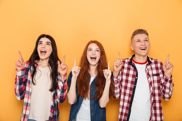 Grupo de amigos felizes da escola apontando o dedo para cima